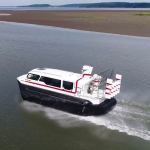 Amphibious Marine Explorer 24 Hovercraft at speed, near saltwater river delta, stern quarter view.