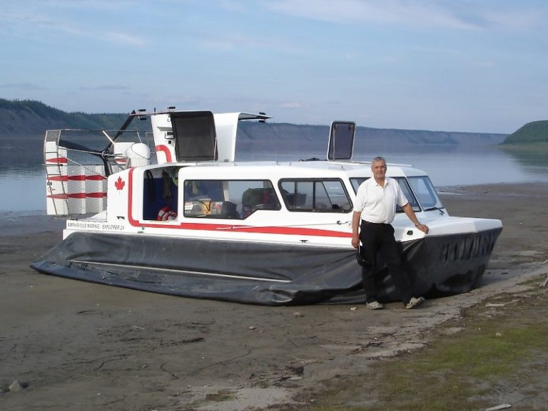 Explorer 24 hovercraft for sale, shown with customer on river bank.